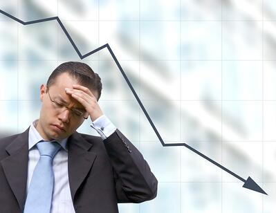 a risk manager stressed over a downward graph background.jpeg