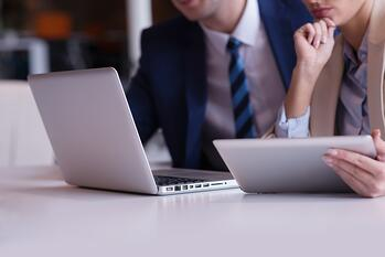 business strategists contemplating market demand analysis on laptop computer